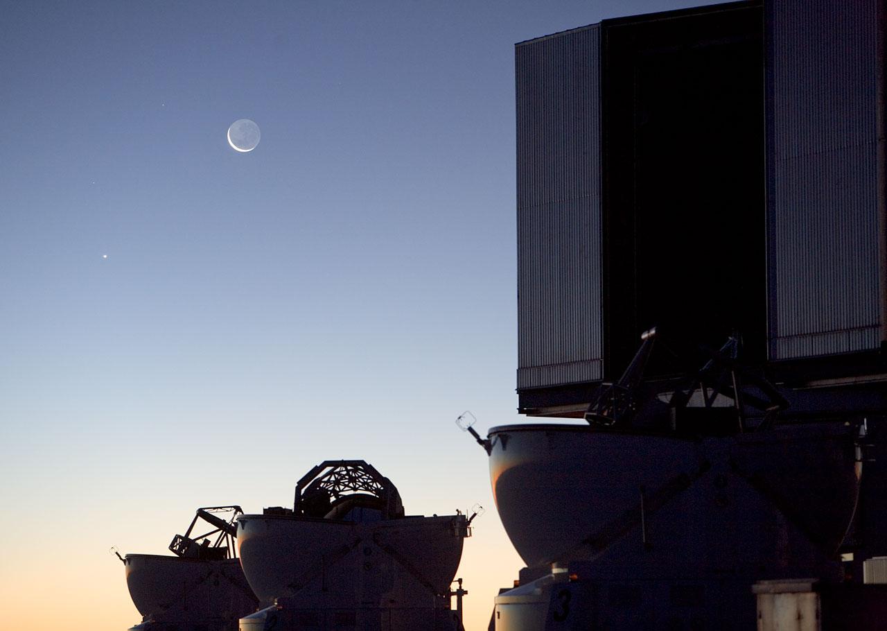 Měsíc poblíž jednoho ze čtyř dalekohledů VLT (vpravo). Na snímku jsou také menší pomocné dalekohledy. Credit: ESO