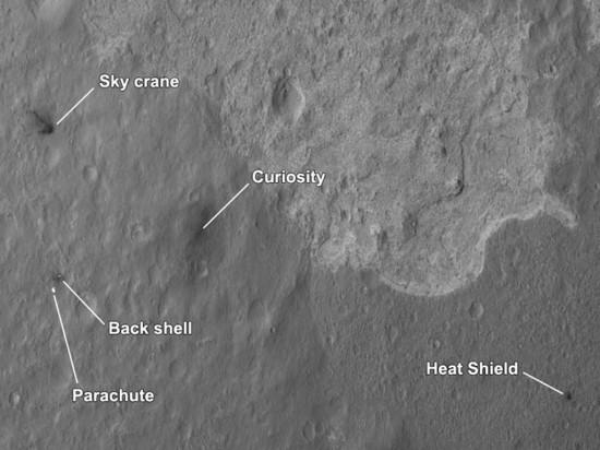Snímek místa přistání z MRO. Vpravo dole tepelný štít, vlevo dole modul s padákem, vlevo nahoře přistávací plošina. Všimněte si, že na snímku jsou vidět tři různé geologické oblasti. Curiosity nepochybně všechny tři prozkoumá, na tiskové konferenci padaly i návrhy na průzkum místa, kde se oblasti stýkají. Credit: NASA