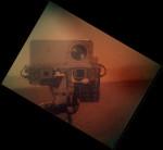 Snímek z kamery MAHLI  zachycuje kolegyně - kamery MastCam a ChemCam. Pokud vám snímek připadá trochu podivně kontrastní, tak je to proto, že byl pořízen skrze clonu, která kameru chrání před prachem. Credit: NASA