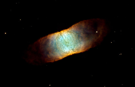 Planetární mlhovina IC 4406.  Důkazy ukazují, že IC 4406 je asi dutý válec a její čtveratý vzhled je výsledkem naší polohy, kdy se na válec díváme ze strany.