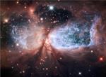 Nebeský anděl. Sharpless 2-106 se nachází ve vzdálenosti 2000 světelných let. Jedná se o mlhovinu, ve které vznikají nové hvězdy. Modrou barvou je znázorněn velmi horký plyn, za tvar může hvězda IRS 4. Credit: NASA, ESA