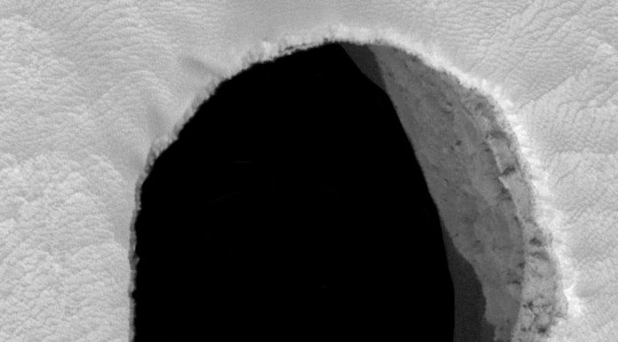 """Jedna z děr, """"vchodů"""" do jeskyně možná až stovky metrů hluboké na svahu Arsia Mons."""