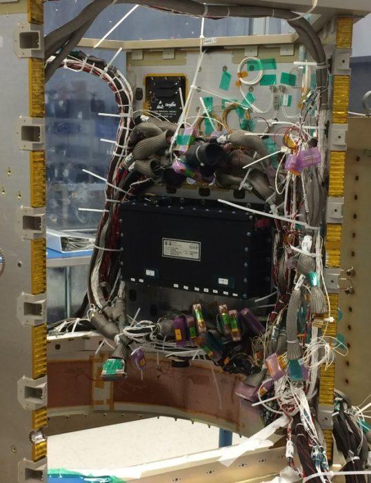 Master Avionics Unit (MAU) od firmy SEAKR Engineering přenáší signály, příkazy a elektrickou energii do ostatních částí družice. MAU je na fotografii ta černá krabice. Credit: NASA